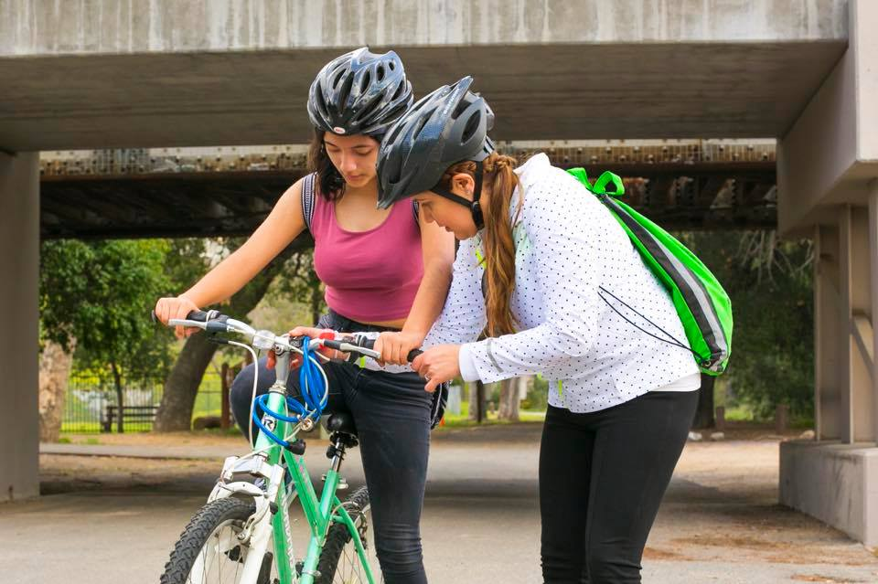 """SAAS member Rosario """"Charis"""" Perez, left, helps Mary Leopo with her bike during a SAASy Mujeres ride."""
